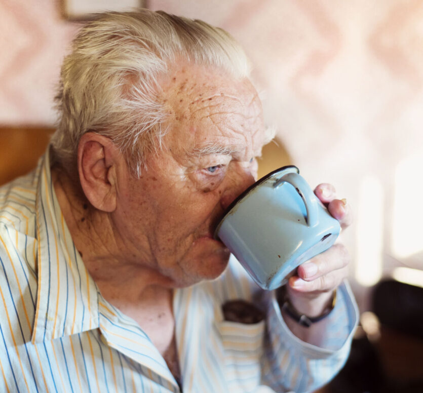 Oude man drinkt uit mok